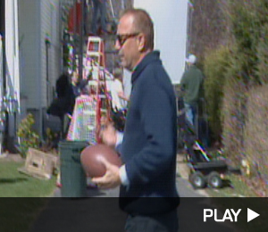 Kevin Costner throws a football on set