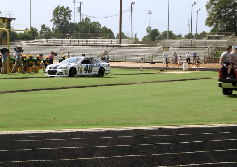 Why Is NASCAR's Jimmie Johnson Driving Onto a High School Football Field?